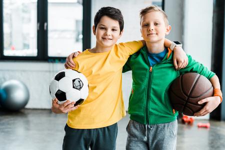 Foto de Pleased boys embracing while posing with balls - Imagen libre de derechos