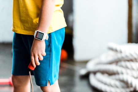 Foto per Partial view of boy in smartwatch holding jump rope - Immagine Royalty Free