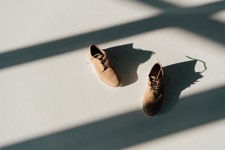 Photo pour pair of beige suede shoes on floor in sunlight with shadows - image libre de droit