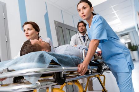 Photo pour Doctors and nurse transporting unconscious patient on gurney - image libre de droit