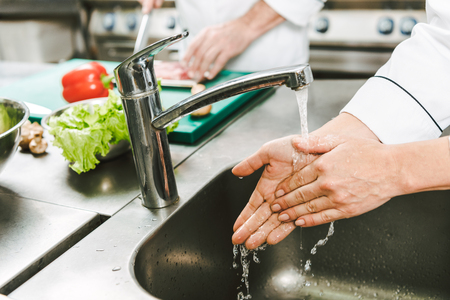 Photo pour cropped view of female chef washing hands over sink in restaurant kitchen - image libre de droit