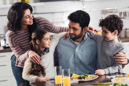 Foto de cheerful hispanic family smiling while hugging near lunch at home - Imagen libre de derechos