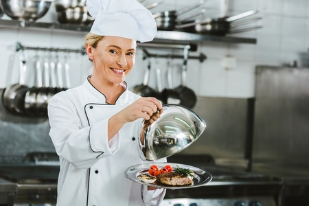 Foto de beautiful smiling female chef in uniform holding dome from serving tray with meat dish in restaurant kitchen - Imagen libre de derechos