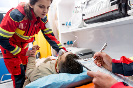 Foto de Cropped view of paramedic writing diagnosis while colleague checking pulse - Imagen libre de derechos
