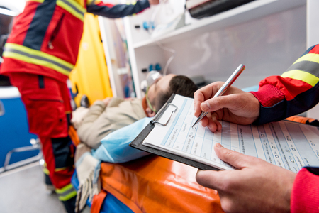 Photo pour Partial view of paramedic writing diagnosis in clipboard - image libre de droit