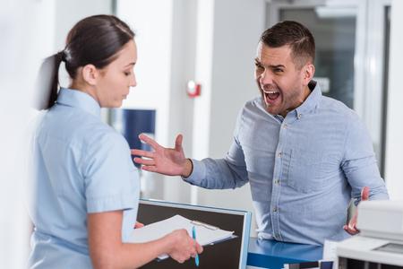 Foto de Aggressive man yelling at nurse in clinic - Imagen libre de derechos