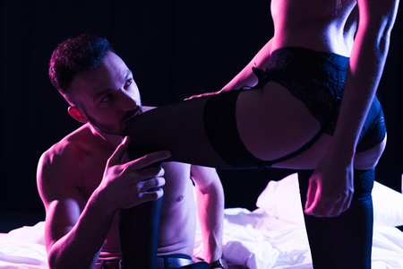Photo pour sexy shirtless man kissing leg of sexy girlfriend standing in underwear near bed isolated on black - image libre de droit