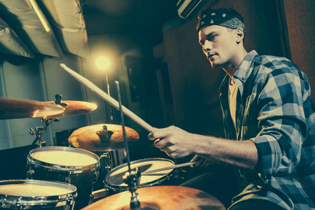 Photo for selective focus of handsome drummer holding drum sticks while playing drums - Royalty Free Image