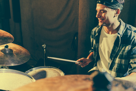 Photo for selective focus of cheerful drummer holding drum sticks while playing drums - Royalty Free Image