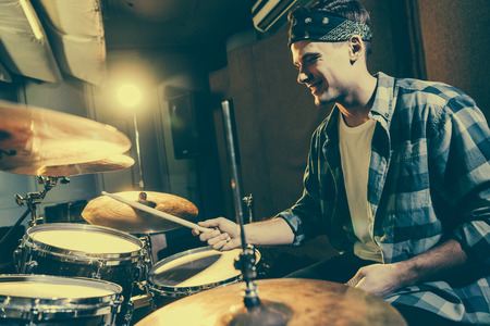 Photo for selective focus of happy drummer holding drum sticks while playing drums - Royalty Free Image