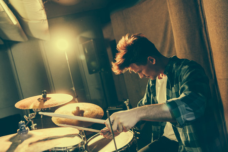 Photo for handsome musician holding drum sticks while playing drums - Royalty Free Image