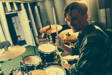 Photo for happy good-looking musician holding drum sticks near drums - Royalty Free Image