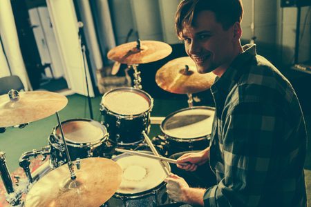Photo for cheerful good-looking musician holding drum sticks near drums - Royalty Free Image