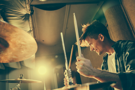 Photo for cheerful good-looking drummer holding drum sticks while playing drums - Royalty Free Image