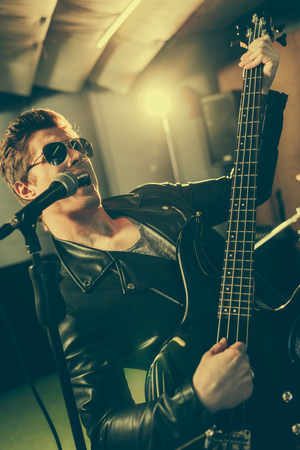 Photo for good-looking guitarist in sunglasses singing song in microphone while playing electic guitar - Royalty Free Image