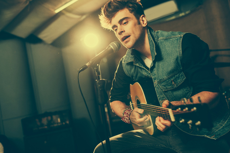 Photo for handsome singer singing in microphone while playing acoustic guitar - Royalty Free Image