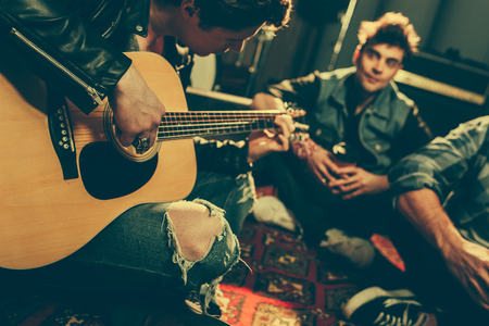 Photo for selective focus of musician playing acoustic guitar near friends - Royalty Free Image