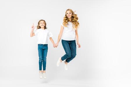 Foto de happy mother with adorable daughter jumping on white background - Imagen libre de derechos
