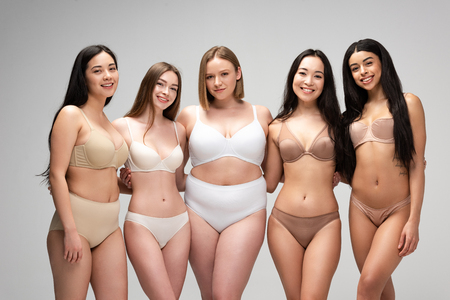 Foto de five beautiful multicultural girls in underwear looking at camera and smiling isolated on grey, body positivity concept - Imagen libre de derechos