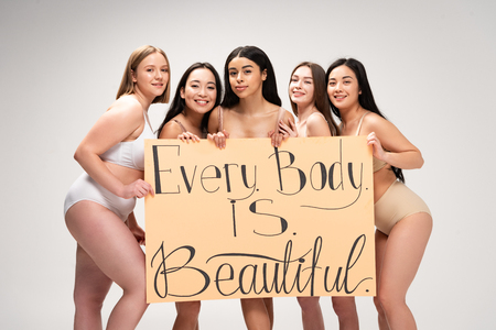 Foto de five smiling multiethnic girls holding placard with every body is beautiful lettering isolated on grey - Imagen libre de derechos
