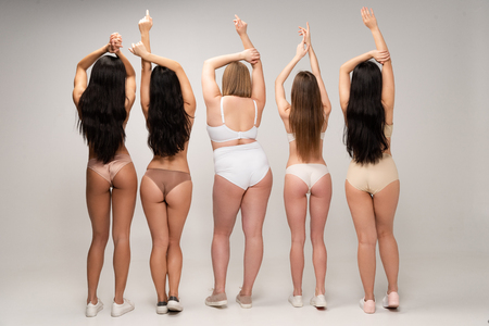 Foto de back view of five multicultural women in lingerie with raised hands, body positivity concept - Imagen libre de derechos