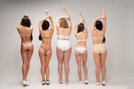 Photo pour back view of five multiethnic women in underwear with raised hands, body positivity concept - image libre de droit