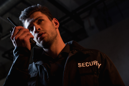 Photo pour handsome guard in uniform using walkie-talkie and looking away - image libre de droit