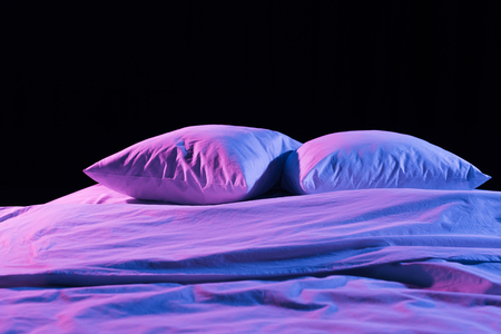 Photo for white pillows and bedding with neon light isolated on black - Royalty Free Image