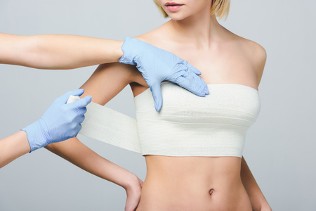 Foto de cropped view of plastic surgeon wrapping female breast with bandage, isolated on grey - Imagen libre de derechos