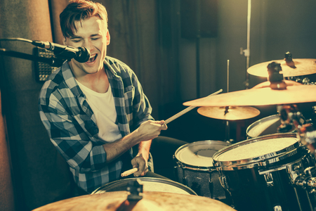 Photo for selective focus of handsome drummer singing in microphone while playing drums - Royalty Free Image