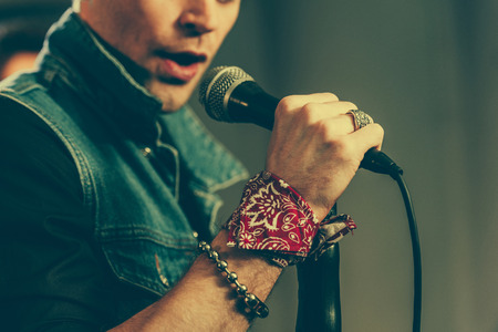 Photo for cropped view of stylish man singing in microphone - Royalty Free Image