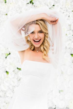 Foto de cheerful young bride holding bridal veil in raised hands on white floral background - Imagen libre de derechos