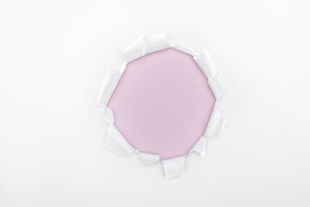 Foto de ripped hole in white textured paper on pink background - Imagen libre de derechos