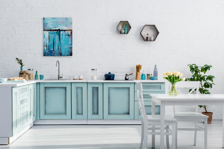 Photo for interior of turquoise and white kitchen full of sunlight - Royalty Free Image