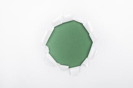 Foto de ragged hole in textured white paper on green background - Imagen libre de derechos
