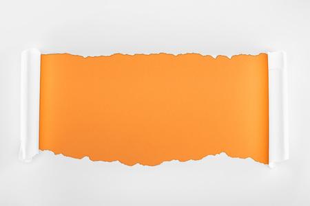 Foto de ragged textured white paper with curl edges on orange background - Imagen libre de derechos