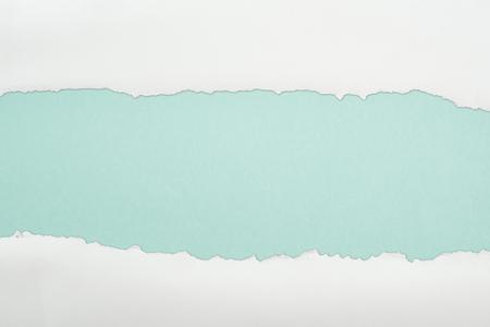 Foto de ragged and white paper with copy space on light blue background - Imagen libre de derechos