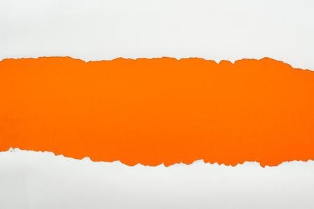 Foto de ripped white textured paper with copy space on orange background - Imagen libre de derechos