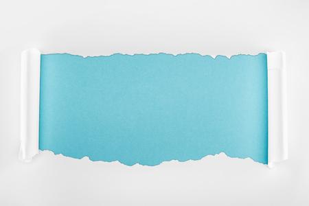 Foto de ripped white paper with curl edges on light blue background - Imagen libre de derechos