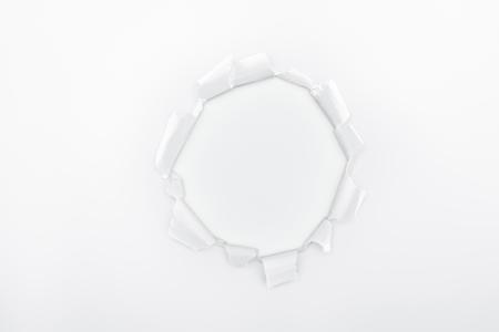 Foto de ragged hole in textured paper on white background - Imagen libre de derechos