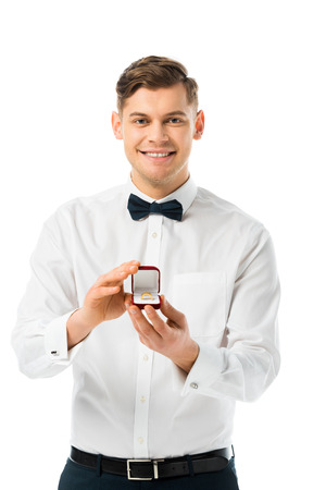 Foto de happy groom demonstrating gift box with wedding ring and looking at camera isolated on white - Imagen libre de derechos