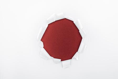 Foto de ragged hole in textured white paper on burgundy background - Imagen libre de derechos