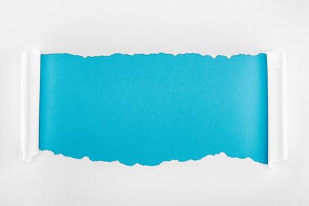 Foto de ripped white paper with curl edges on blue background - Imagen libre de derechos