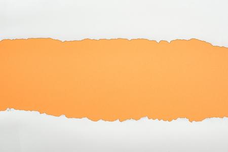 Foto de ragged white textured paper with copy space on orange background - Imagen libre de derechos