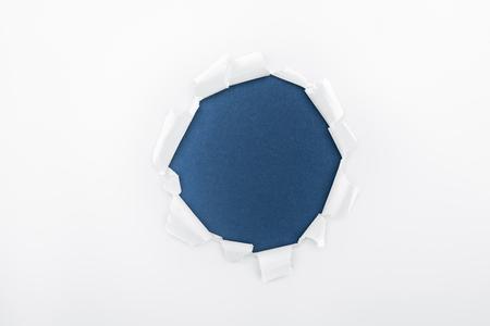 Foto de ragged hole in textured white paper on dark blue background - Imagen libre de derechos