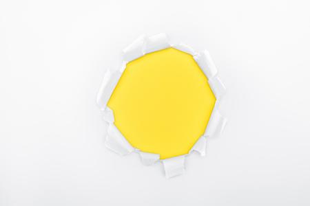 Foto de torn hole in white textured paper on yellow background - Imagen libre de derechos
