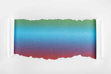 Foto de ragged white paper with curl edges on multicolored background - Imagen libre de derechos