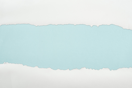 Foto de ripped white textured paper with copy space on light blue background - Imagen libre de derechos
