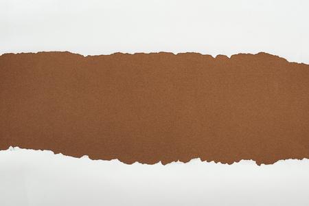 Foto de ragged white paper with curl edges on brown background - Imagen libre de derechos