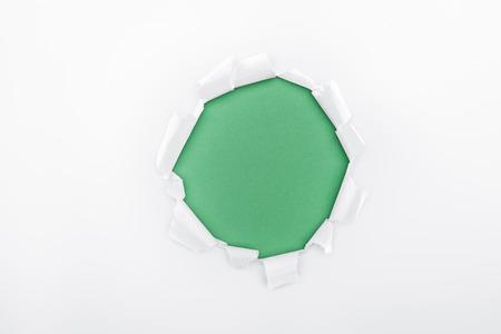 Foto de torn hole in white textured paper on green background - Imagen libre de derechos